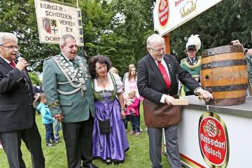 Schirmherr Heinz Krosch sticht das erste Fass an: Das Dormagener Schützenfest ist eröffnet. BSV-Vorsitzender Rolf Starke (l.) moderierte. FOTO: Linda Hammer